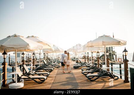 Una pareja amorosa está descansando en el mar en Turquía. Hombre y mujer en el muelle. Paseo marítimo. Luna de miel. Una pareja en un viaje de luna de miel. Un hermoso viaje en pareja