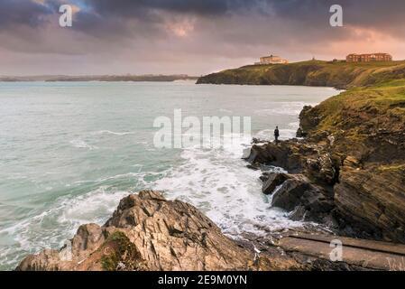 Luz nocturna cálida sobre un pescador pescando en rocas en la costa de Newquay Bay en Cornwall.