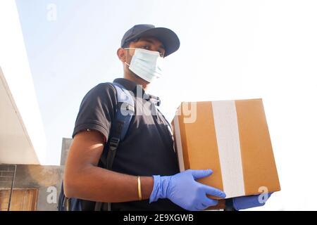 Retrato de un joven hombre de entrega de la India con caja de cartón