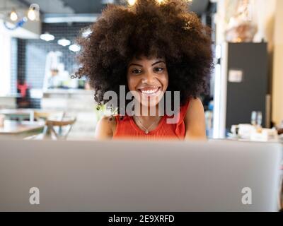 Mujer negra encantada freelancer sentado en el café y navegando netbook mientras trabaja de forma remota en proyectos en línea