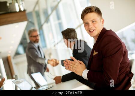 Un hombre joven y guapo golpeando las manos después de una exitosa reunión de negocios la oficina moderna