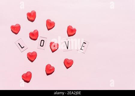 Banner.la palabra Amor.letras negras Amor con corazones rojos.sobre fondo rosa.día de San Valentín. Emociones amorosas y positivas. Sentimientos de fondo. Exclusivo