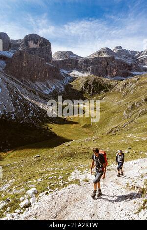 Excursionistas en el valle de Zwischenkofel con el pasto alpino Antersasc debajo de los picos de Puez en el sol de la mañana, Dolomitas Grupo Puez-Odle, Tirol del Sur