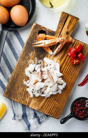 Ingrediente de tortilla española o tailandesa, Chile rojo fresco, carne de cangrejo marrón y blanca, limón, queso Cheddar, huevos, sobre fondo blanco, vista superior plano