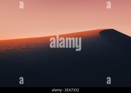 La luz ambiental y mística de la luz del sol de la puesta de sol se ilumina la pendiente de una duna de arena en alguna parte en las profundidades Del desierto del Sáhara