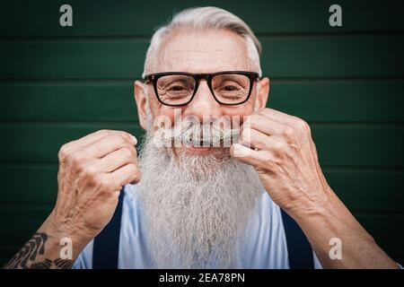 Retrato de un hombre mayor feliz de cintura baja con fondo verde - Concéntrate en el bigote