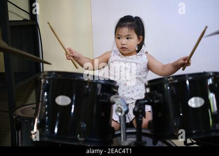 Una linda joven asiática está practicando con su batería, sosteniendo palillos de batería en ambas manos, golpeando su batería y platillos.
