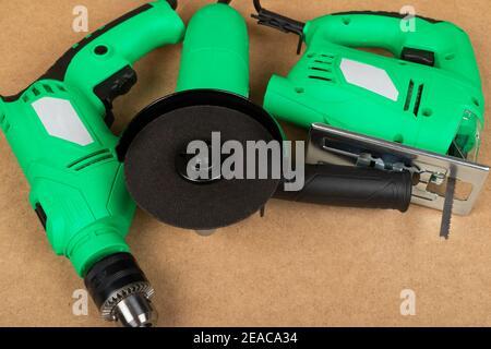 Imagen de una sierra verde de la jig y un taladro y. amoladora angular sobre fondo de madera