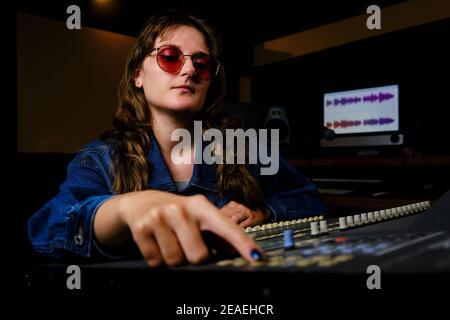 Mujer ingeniera de sonido en la mezcladora en el estudio de música. Mujer en gafas de sol y jeans detrás de la consola de mezcla en el estudio de grabación.