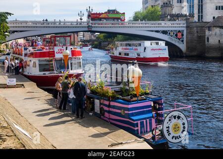 Atracciones para visitantes en York por el pintoresco río Ouse (pasajeros a bordo y navegación en barcos de crucero, autobús turístico, vendedor de helados) - North Yorkshire, Inglaterra Reino Unido. Foto de stock