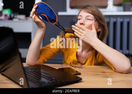 Mujer caucásica durmiendo en máscara de sueño sentada en la mesa de madera, después de trabajar cansada frente a la computadora con un smartphone cerca de ella. Alarma de mañana