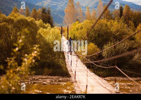 Hombre irreconocible caminando con moto de campo a través en el puente colgante sobre el río de las montañas en verano