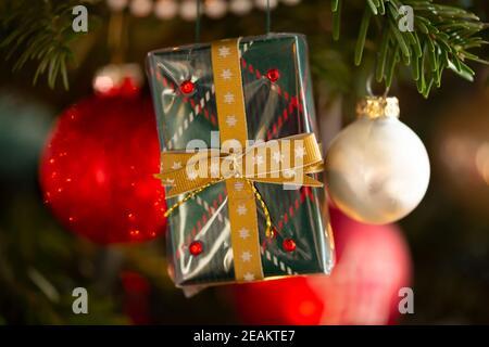 Árbol de Navidad decorado, abeto real Nordmann frente a fondo borroso. La fotografía macro muestra un regalo envuelto hecho a mano.