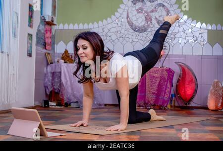Hermosa mujer mayor activa haciendo ejercicio o dando clases en línea en casa en la computadora portátil durante la cuarentena. Yoga Posición de tigre o Vyaghrasana.