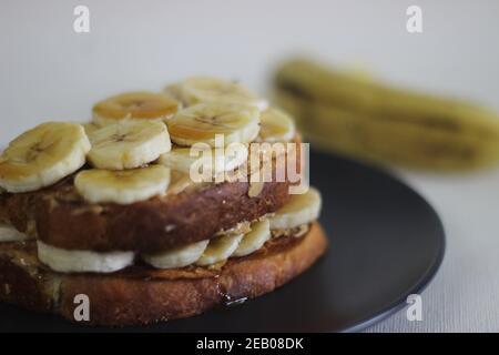 Sándwich de mantequilla de maní plátano miel de pan tostado, una idea de desayuno fácil. Grabado sobre fondo blanco.