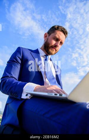 Hombre de negocios navegando por Internet o responder correos electrónicos mientras se sienta con el portátil al aire libre. Aumentar las sugerencias de ventas en línea. Consejos para crear correos electrónicos fríos increíbles. El gerente de ventas trabaja en el fondo azul del cielo de la comercialización del Internet.