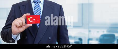 Imagen recortada de un hombre de negocios con tarjeta de crédito de plástico con bandera impresa de Turquía. Fondo borroso.