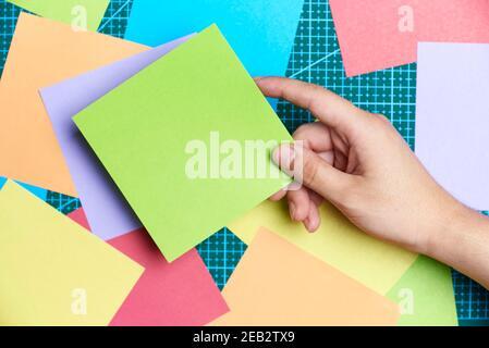 Mano joven de mujer sosteniendo un cuadrado de papel verde en blanco sobre otros papeles coloreados y una estera de corte. Material para escribir notas o hacer origami o o.