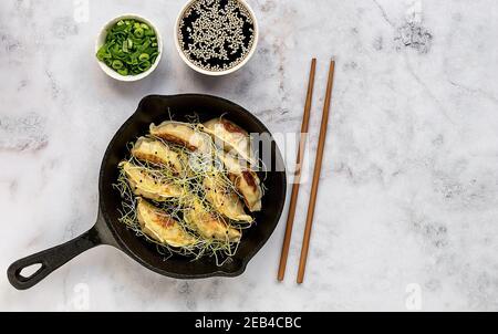 Dumplings vegetarianos asiáticos Gyozas fritos en una sartén de hierro fundido, servidos con palillos
