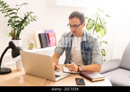 Un joven empresario centrado en la realización de una videollamada con los clientes en el ordenador portátil. Hombre milenario concentrado en gafas dando clases educativas en línea