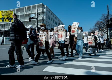 Tokio, Japón. 14 de febrero de 2021. Los manifestantes sostienen pancartas mientras marchaban en la calle durante la manifestación.los manifestantes birmanos se reunieron cerca del Parque Yoyogi y marcharon hacia Shibuya para protestar contra el golpe militar y exigieron la liberación de Aung San Suu Kyi. El ejército de Myanmar detuvo a la Consejera de Estado de Myanmar, Aung San Suu Kyi, el 01 de febrero de 2021, y declaró el estado de emergencia mientras se apoderaba del poder en el país durante un año después de perder las elecciones contra la Liga Nacional para la Democracia (LND). Crédito: SOPA Images Limited/Alamy Live News