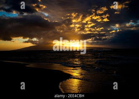 Paisaje marino al atardecer dorado con rayos de luz que brota desde debajo de las nubes mientras el sol se pone detrás de la isla tropical.