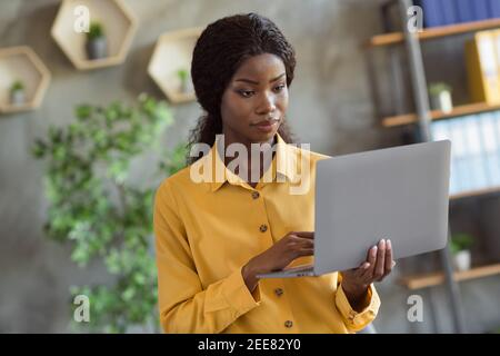 Foto retrato de una niña afroamericana trabajando en la sujeción de un portátil en las manos en la oficina moderna en interiores