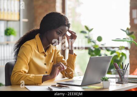 Foto retrato de una mujer afroamericana tocando la cabeza trabajando ordenador portátil en una oficina moderna en interiores Foto de stock