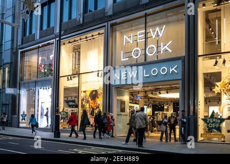 Ropa de nueva apariencia moderna centro de la ciudad tienda con Marca logo y letrero iluminado por la noche ocupado con los turistas y compradores Foto de stock