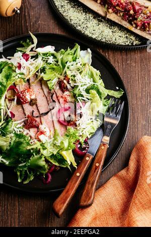 Ensalada fresca y sabrosa de Persimmon con arúgula, jamón de parma, aceite de oliva y hierbas. Otoño, invierno foo saludable