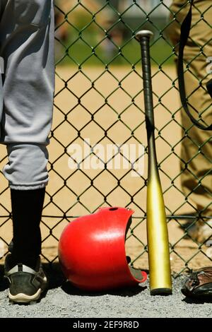 Vista de sección baja de dos chicos de pie a ambos lados de una cerca de cadena-eslabón