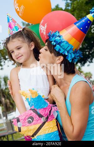 Perfil lateral de una mujer adulta mediana besando a su hija Foto de stock
