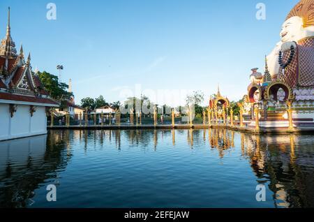 KOH SAMUI, TAILANDIA - 10 de enero de 2020: Mujer en un vestido rojo de pie en un puente a una estatua gigante de Buda colorido en el templo de Wat plai laem en koh