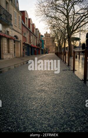 Calle vacía por la noche en la rochelle, Francia. Torre de San Nicolás en el fondo