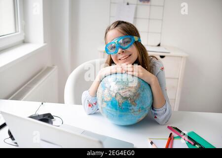 cute rubia chica está sentada en la mesa frente a la laptop, sosteniendo globo en sus manos, tiene gafas de buceo o gafas de natación y sueña con vacati
