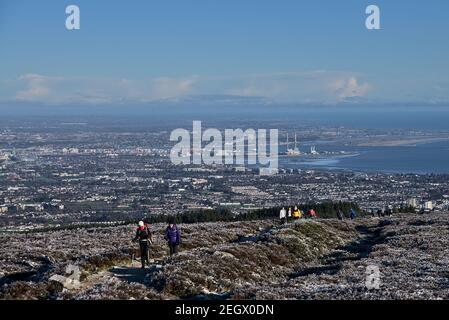 Gente que se encuentra caminando durante el encierro de coronavirus para ver el invierno irlandés inusual y los paisajes de Dublín y las montañas de Wicklow. Visto desde el castillo de hadas (dos rocas