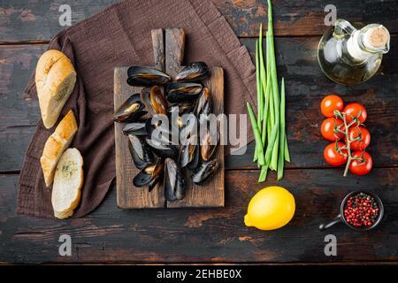Guiso de mejillones en vino blanco y hierbas, sobre tabla de madera, sobre el fondo de la mesa de madera oscura, vista superior plana Lay