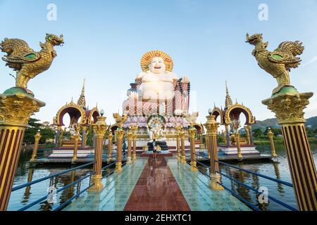 KOH SAMUI, TAILANDIA - 10 de enero de 2020: El hombre con una cámara se encuentra en un puente a una estatua gigante y colorida de buda en el templo de Wat plai laem en koh samui