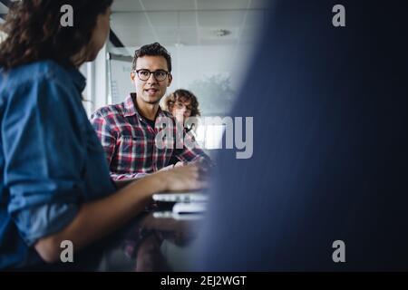Hombre compartiendo sus puntos de vista con colegas durante la reunión. Hombres de negocios y mujeres de negocios que tienen sesión de lluvia de ideas en la sala de juntas de la oficina.
