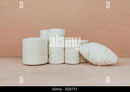 Conjunto de hilo de tejer blanco sobre fondo beige. Hilos de algodón de diferentes tamaños.