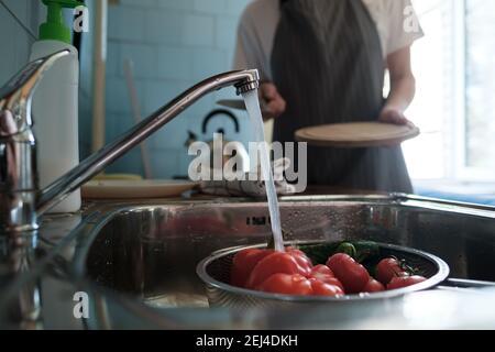 Verduras frescas bajo el agua corriente en un colador en el fregadero, contra el fondo de una esposa con un cuchillo y una tabla de cortar.
