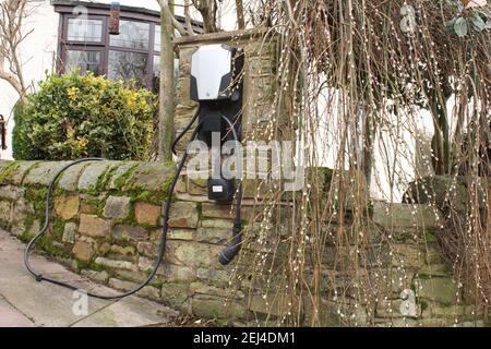 Punto de carga eléctrica doméstica en una pared de piedra, equipo de carga de coche eléctrico Reino Unido Foto de stock