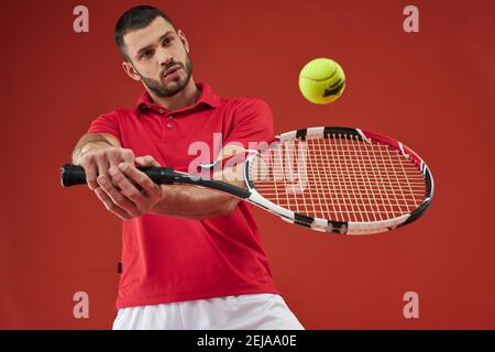 Retrato de cintura arriba de guapo macho con barba caucásica en rojo camisa que sostiene la raqueta en los brazos mientras entrena técnica de agarre de la mano delantera en la cancha cubierta