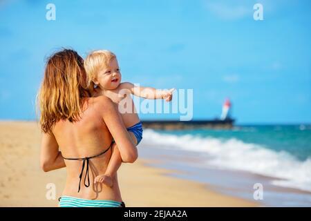 Reírse feliz retrato de niño pequeño mirar y reír punto de hombro con dedo al mar de una madre pararse en la playa