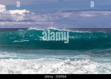 Ondulado en la playa hawaiana. Aerosol volando de vuelta en la parte superior de la ola. Espuma de la onda anterior en primer plano. Aerosol blanco de mar tirado al aire.