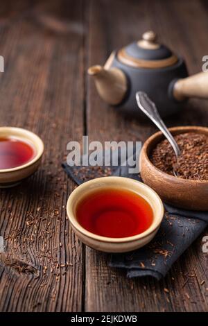 Té de Rooibos recién hecho lleno de antioxidantes sobre fondo de madera