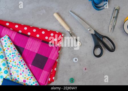 Tela, botones, cremallera, cinta métrica, herramientas de un sastre en una mesa
