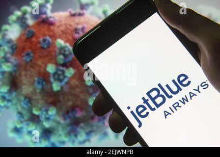 En esta ilustración de la foto se muestra el logotipo de la aerolínea estadounidense de bajo coste JetBlue Airways en un smartphone con un modelo de ordenador del coronavirus COVID-19 en el fondo. (Foto de Budrul Chukrut / SOPA Images/Sipa USA)