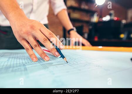 los ingenieros que sostienen un bolígrafo que señala un edificio y el diseño de un plan de construcción de los desembolsos como guía para los constructores con detalles. Diseño y escritura del ingeniero b Foto de stock