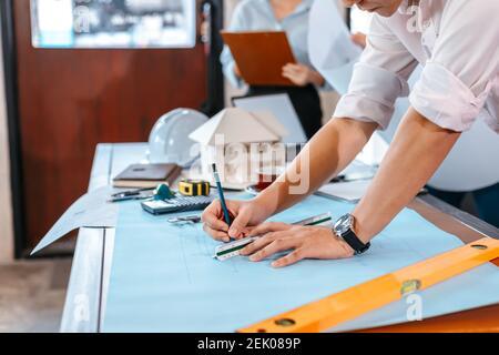 los ingenieros que sostienen un bolígrafo que señala un edificio y el diseño de un plan de construcción de los desembolsos como guía para los constructores con detalles. Diseño y escritura del ingeniero b
